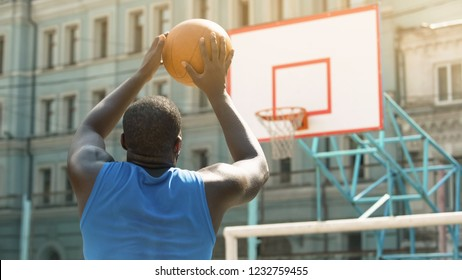 Skilled Afro-American person throwing ball into basket, active sports hobby