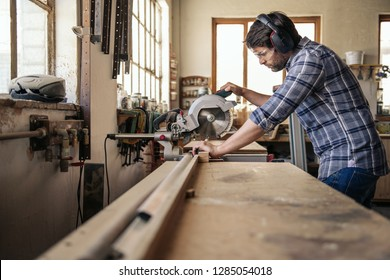 Skilled carpenter wearing safety gear sawing a piece of wood with a mitre saw while working alone in his woodworking studio
