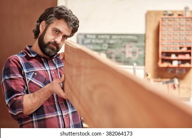 Skilled carpentry craftsman looking expertly down the length of a plank of wood, checking it for quality and straightness, with his workshop in the background