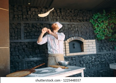 Skilled chef preparing dough for pizza rolling with hands and throwing up