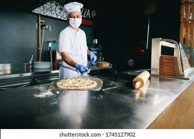 Skilled chef preparing traditional italian pizza  in interior of modern restaurant kitchen with special wood fired oven Wearing protective medical face mask and gloves in coronavirus new normal concep