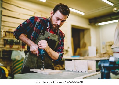 Skilled craftsman in apron using drill while working with wooden plank for furniture in own workshop store, bearded guy carpenter using modern electric equipment for repair and restoration timber
