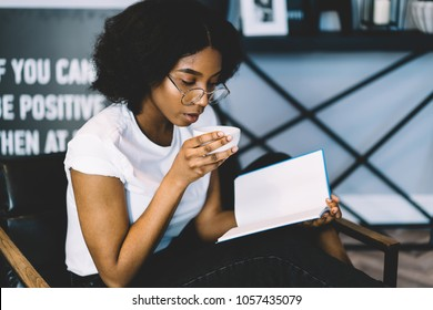 Skilled dark skinned student enjoying tasty coffee while concentrated on reading interesting literature book.Pensive african american young woman spending leisure time on bestseller resting at home