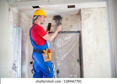 Skilled electrician using unimer for voltage checking