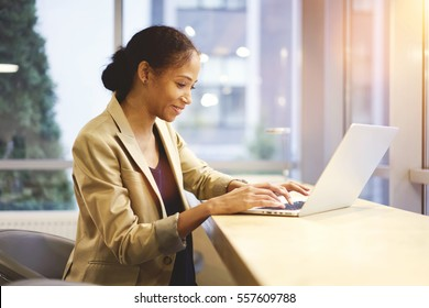 Skilled experienced afro american female executive manager having online conversation with employee making remote job being in business trip using laptop and wifi sitting on copy space for advertising