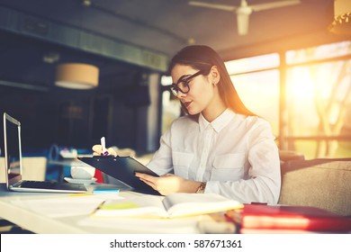 Skilled experienced female owner of restaurant making checklist of duties for stuff  to increase income developing successful strategy for business while sitting at table using laptop computer