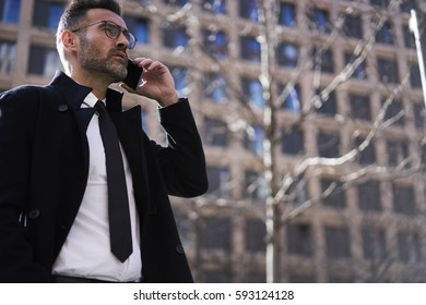 Skilled experienced male entrepreneur in formal outfit booking hotel through phone conversation arranging accommodation during business trip while standing outdoors on urban setting background