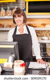 Skilled female baker is standing at the counter near pastry. The woman is looking at the camera with joy and smiling