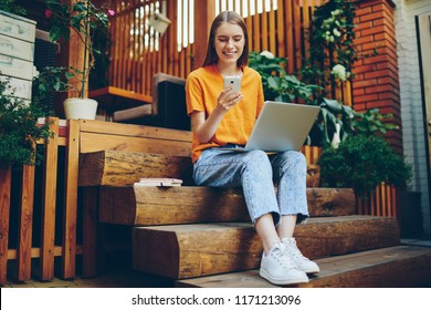 Skilled female blogger with smile on face using smartphone for chatting with followers and enjoying time at cozy cafeteria, cheerful woman happy from reading good news in social network on cellular