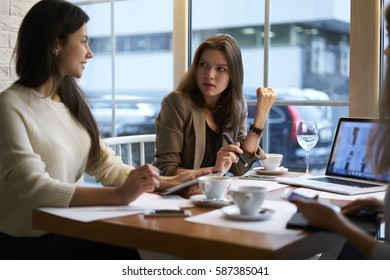 Skilled female CEO of marketing company having informal meeting with colleagues to discuss mistakes in work on advertising campaign for web store presenting creative solutions on laptop computer  - Shutterstock ID 587385041