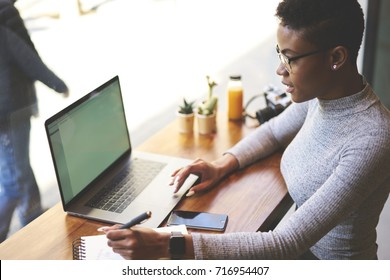 Skilled female copywriter browsing information for making researches writing ideas in notepad spending time in cafe interior, professional freelancer satisfied with working schedule and occupation