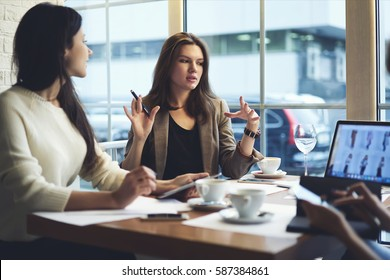Skilled female leader of marketing experts working group explaining successful strategy for startup project to attract followers to online web store while having meeting with colleagues in cafe