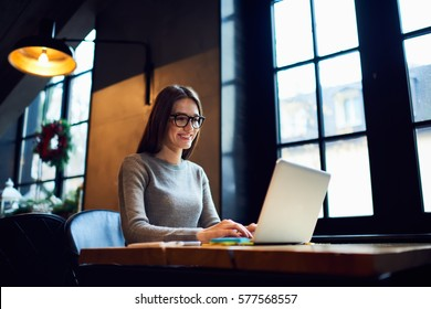 Skilled female software developer working on freelance use code libraries to simplify the transcription cooperating with advanced programmers adapt  application to systems platforms via laptop