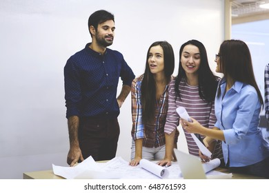 Skilled female students having consultancy with professional coach checking graphic outlay  for architect project giving advice and improving idea of planning,crew of colleagues brainstorming together
