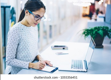 Skilled female web designer creating sketch on touchpad synchronized with laptop computer, professional administrative manager signing online documentation on tablet working with clients base