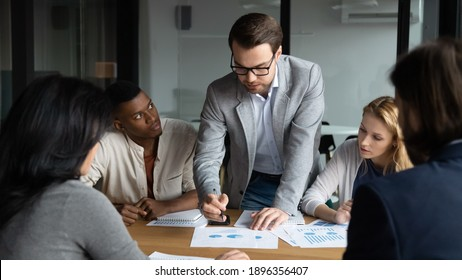 Skilled focused young businessman boss leader in eyeglasses analyzing sales data statistics or explaining marketing strategy to motivated diverse multiracial colleagues at brainstorming meeting.