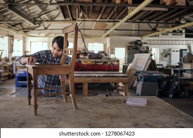 Skilled furniture maker sanding a wooden chair on a workbench while working alone in his large woodworking shop