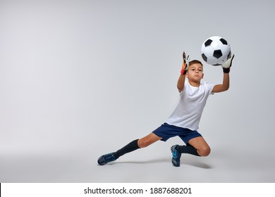 skilled goalkeeper boy get the ball in hands while defending football goal. isolated white background