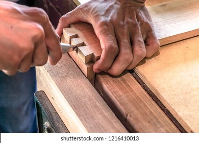 Skilled joiner working in carpentry. Amateur woodworker making dovetail join for wooden drawer in carpenters workshop