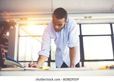 Skilled male afro american engineer thinking over blueprint improvement noting ideas in copy book to correct mistakes in planning looking concentrated on workspace desk with papers in modern studio