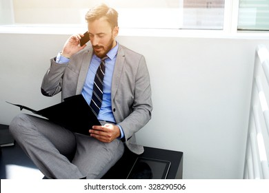 Skilled male calling with cell telephone while reading important information in paper documents, young men financier having mobile phone conversation while sitting with dossier files in office space