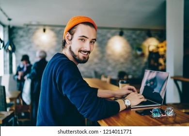 Skilled male it developer looking at camera coding on modern laptop computer working on freelance in cafe interior, portrait of cheerful hipster guy using netbook for e learning satisfied with course