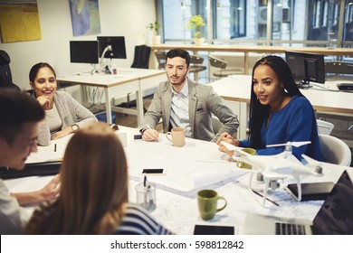 Skilled male and female colleagues collaborating working on start up project discussing ideas and making strategy plan during informal meeting listening to reportings and explanations attentively
