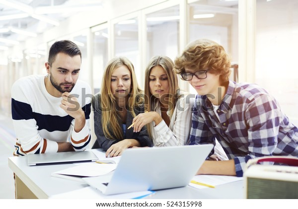 Skilled male and female programmers watching webinar about software development brainstorming innovating ideas for outsourcing using modern laptop computers fast 4G net connection working in office
