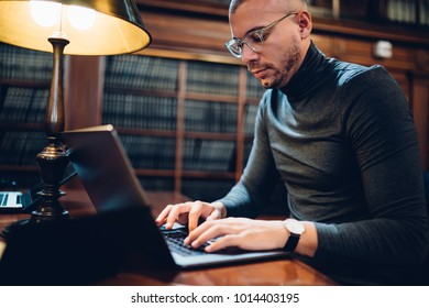 Skilled male journalist in eyewear typing text of article on laptop computer for publication working in book archive, pensive professor of literature browsing web page on netbook using wifi in library