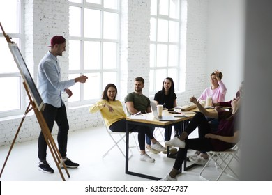 Skilled male marketing expert presenting creative ideas for advertising campaign to group of colleagues during meeting in office, coworkers sharing opinions during brainstorming session in good mood