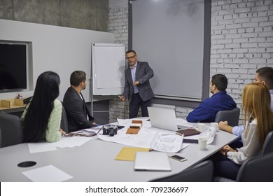 Skilled mature coach in eyeglasses making training for colleagues members of dream team and explaining general working concepts.Experienced male manager provides consultancy on formal meeting