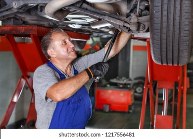 Skilled mechanic technician working in service station, repairing a car
