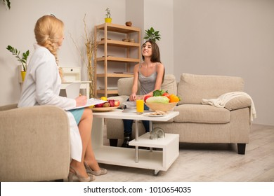 Skilled nutritionist and smiling patient having conversation.