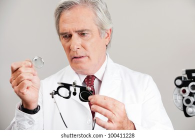 Skilled optometrist examining the lens while holding trial frame for an eye checkup