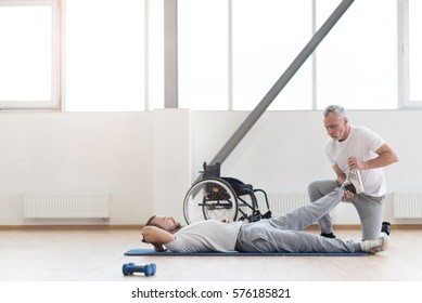 Skilled orthopedist working out with disabled patient in the gym