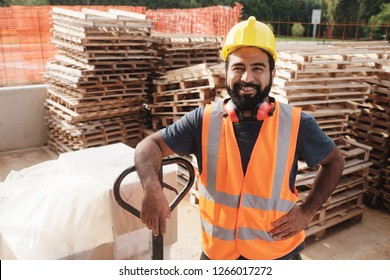 Skilled people working in construction site. Hispanic man at work in new house. Portrait of happy latino worker using manual forklift to move hardware and smiling at camera