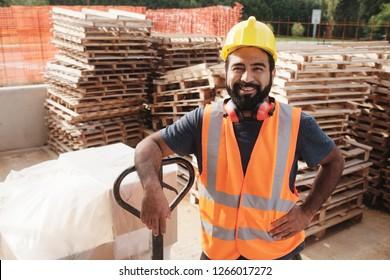 Geschickte Menschen, die auf Baustellen arbeiten. Hispanischer Mann bei der Arbeit in einem neuen Haus. Portrait von glücklichen Latino-Mitarbeiter mit manuellem Gabelstapler, um Hardware zu bewegen und bei der Kamera lächeln