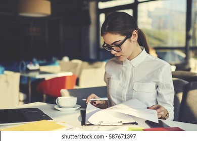 Skilled professional female administrative manager of coffee shop checking documentation for month before sending report to financier supervising working process and controlling stuff during revision