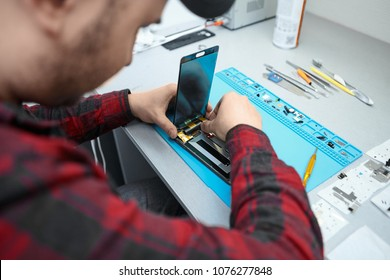 Skilled professional male technician from electronics repair service removing screen glass from mobile phone. Back view of repairman disassembling electronic gadget, fixing faults inside it