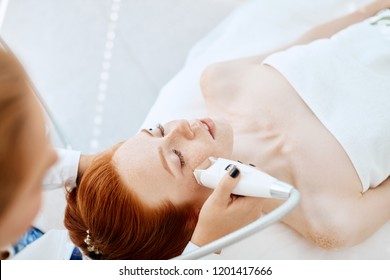 Skilled professional mature female beautician in white uniform performing photo rejuvenation cosmetology procedure for a red haired caucasian woman lying on the coach in beauty centre.