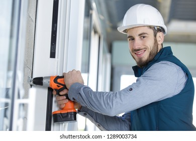 skilled professional using electric drill on the window