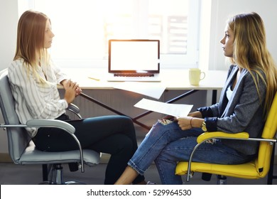 Skilled recruiter making job interview with female student for IT occupation,reading paper cv while sitting in modern office with free internet access and laptop computer with blank mock up screen