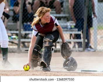 Skilled softball catcher with red hair and protective gear gaining a grip on the loose ball while looking up field.