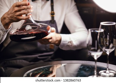 Skilled sommelier holding decanter with red wine. Degustation of wine process in wine boutique, close up.