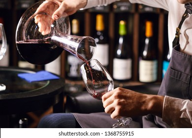 Skilled sommelier pouring wine from decanter into wine glass. Degustation of wine process in wine boutique, close up.