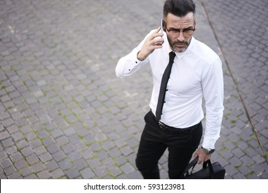 Skilled successful male economist receiving phone call from executive inviting him to informal meeting table for discussing solution of law rate of sales and incomes while he going for work in morning