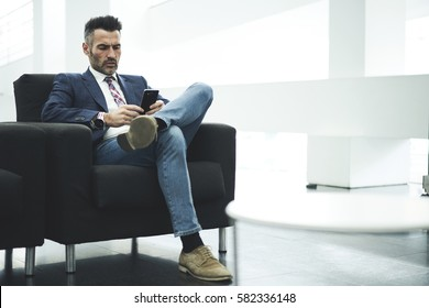 Skilled successful male owner of trading corporation reading notification of working day schedule on smartphone connected to wireless internet while sitting in office preparing for conference meeting