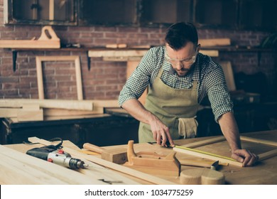 Skilled talented bearded busy confident bearded handyman clothed in checkered casual shirt apron protective glasses is measuring the wooden frame's length on his desktop with a roulette
