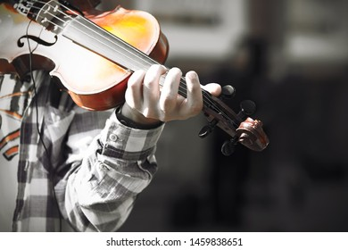 A skilled violinist, dressed in a plaid shirt and a white t-shirt with an orange pattern, plays a melody on an old beautiful violin.