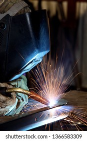 A skilled welder arc welding two pieces of metal together at a metal fabrication plant.